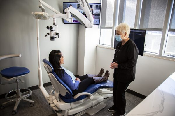 dental assistant talks with a patient